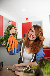 Young woman holding bunch of carrots at kitchen, Munich, Bavaria, Germany