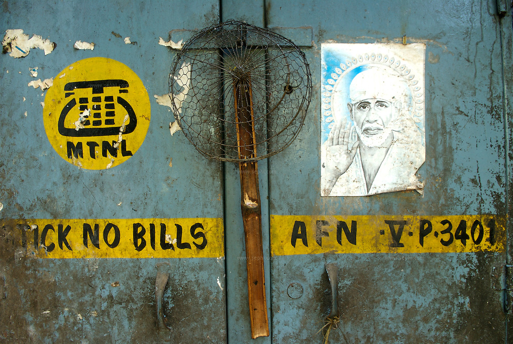 A sieve and a poster of Sai Baba (A hindu saint) on the local telephone company service box behind a chinese food stall in south Mumbai, June 2007