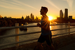 © Licensed to London News Pictures. 24/09/2018. London, UK. A jogger runs across Waterloo Bridge during sunrise on the River Thames during cold but sunny weather this morning.  Photo credit: Vickie Flores/LNP