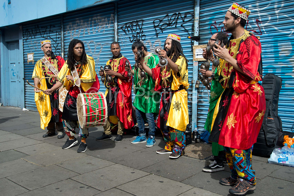 Notting Hill Carnival 2016 Childrens Day. A group of musicians wearing brightly coloured robes play on Portobello Road.