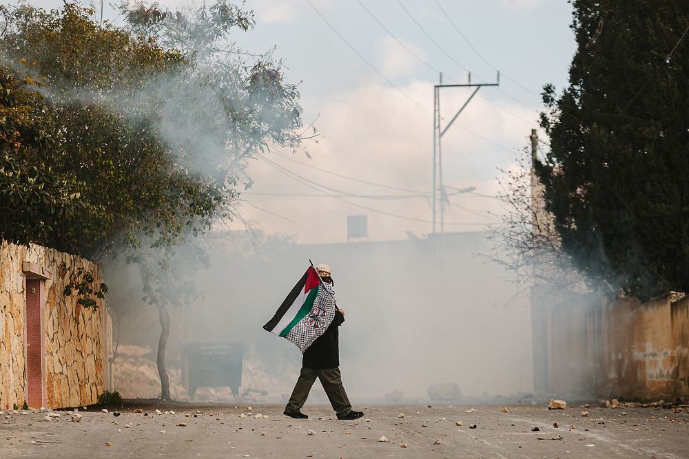 A Palestinian man wearing a gas mask and carrying the Palestinian national flag in his hand is seen shrouded by a cloud of tear gas fired by Israeli forces, during a weekly demonstration against the expropriation of Palestinian land by Israel and against the closure of the main road leading to Nablus, in the Palestinian village of Kufr Qaddum, West Bank, on February 21, 2020.