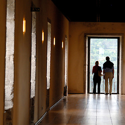 Santa Maria Do Bourho, Portugal - A couple visiting the former Cistercian monastery of Santa Maria Do Bourho look out a window onto the landscape surrounding the monastery from one of the large interior corridors that formerly led to monk's quarters and now guest rooms...Photo by Susana Raab