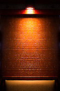 Light shining on a textured wooden stained wall in a bar <br /> <br /> Editions:- Open Edition Print / Stock Image