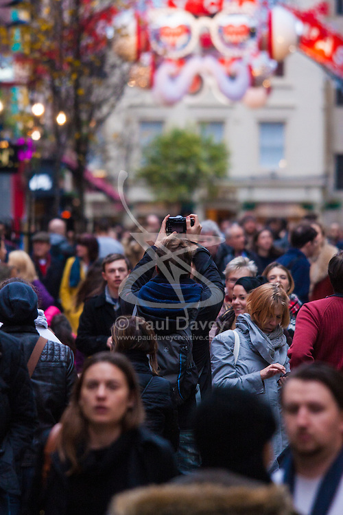 "London, December 23rd 2014. Dubbed by retailers as the ""Golden Hour"" thousands of shoppers use their lunch hour to do some last minute Christmas shopping in London's West End. PICTURED: A man takes a high level shot of the crowds on Carnaby Street."