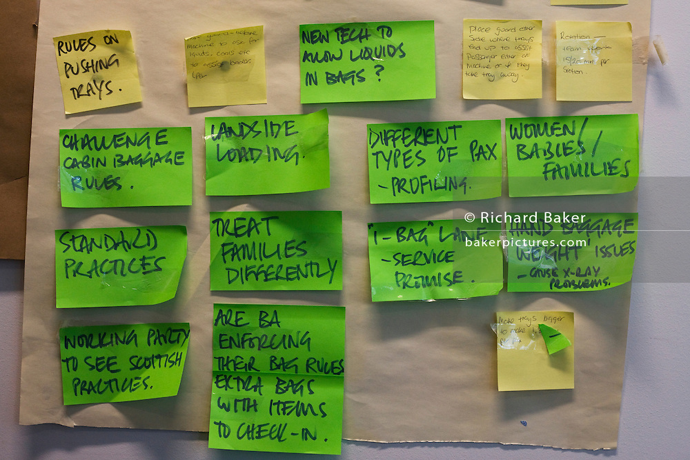 Post-it notes are fixed to an office wall during a brainstorming session in central London.