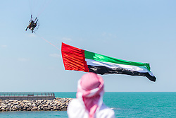 March 5, 2019 - Ras Al Khaimah, Ras Al Khaimah, United Arab Emirates - A local Emirati man seen looking on as a paraglider with the UAE national flag flies over Al Marjan Island, during the event..The Special Olympics World Games 2019 will be hosted in Abu Dhabi, United Arab Emirates in March 2019 for the first time in the Middle East and North Africa since the movement's founding over 50 years ago. The final stage of the Special Olympics Law Enforcement Torch Run was held on Al Marjan Island, Ras Al Khaimah. The event was celebrated with traditional Emirati music and dances. The CEO of Marjan and Master Developer of Ras Al Khaimah, Mr Abdulla Al Abdouli opened the event. (Credit Image: © Mike Hook/SOPA Images via ZUMA Wire)