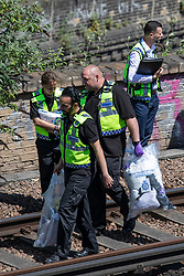© Licensed to London News Pictures. 18/06/2018. London, UK. Police officers are seen carrying evidence bags on the train tracks near Loughborough Junction station where three bodies were discovered after they were reportedly hit by a train. Photo credit: Rob Pinney/LNP
