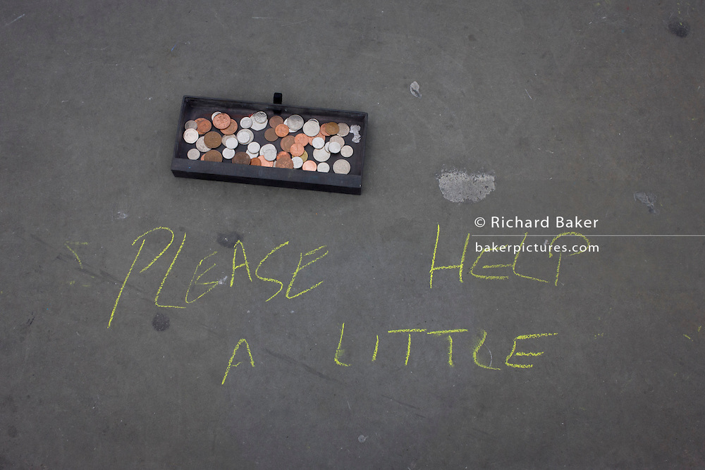 Busker's message in chalk and donation coins on pavement in Trafalgar Square.