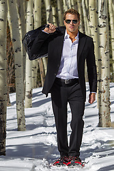 hot man dressed in a suit walking in the snow with snow shoes