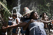 Every year thousands of devotees seek fortune in the goddess Erzulie<br /> <br /> At 150 kilometers from Port au Prince, Haiti's capital, a waterfall flows. Thousands of pilgrims come to the place where they say appeared Erzulie, the goddess of love and beauty then camouflaged in the Virgin of Miracles. The offering becomes a ritual show in search of fortune in the poorest country of America, beaten in 2010 by earthquakes, disease and misery.<br /> <br /> Every year, thousands of pilgrims who have saved recent months to afford the cost of travel-the waterfall is 150 kilometers north of Puerto Principe move there, walk for hours to the waterfall and allowed to bathe in its waters. Bodies, songs and the most common in voodoo celebrations, weird music mixed with scents of herbs and potions prepared to ask favors from the spirits. Believers spend hours in the sound and the freshness of the water, praying, hugging. Many throw their old clothes to the sky, a symbol of a past they want to leave behind. And some consult their hougan (priests) or mambo (priestess), owned by the loas (voodoo deities. Thousands of faithful, including children and pregnant women huddle under a waterfall for the bathroom of luck and invoked the . Ezili Ewa figure, one of the main characters of the voodoo pantheon Under the waterspout is impossible to hear a word, the devotees dance, make ablution with bottles and bowls of pumpkin and delivered to communion with saints 'praise'. These are baroque and colonial names as Baron Samedi, Brigitte Maman, Papa Legba, Damballa and Papa Ogou.<br /> According to popular legend, in 1847 Erzulie Dantor, voodoo goddess of beauty and love, appeared on a tree, in this cascade, and began to heal the sick and perform miracles. Catholic priests saw this as blasphemy and ordered to cut down the trunk, erecting a few meters from a church in honor of the Virgin. By Haitian art work and syncretism, Erzulie is camouflaged in the Catholic Our Lady of Miracles. Since then
