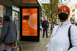 © Licensed to London News Pictures. 26/10/2020. London, UK. A woman wearing a face covering at a bus stop where a COVID-19 high alert level sign is displayed  in north London. It has been reported that the government is planning for an extra tougher fourth tier of Covid-19 restrictions in England if coronavirus cases increase in the coming weeks. The measures could see restaurants, pubs and non-essential businesses such as clothes shops forced to close in areas where tier 3 rules have not brought the virus under control. Currently all 32 boroughs plus the City of London are in tier two, where there is a high risk of coronavirus. Photo credit: Dinendra Haria/LNP