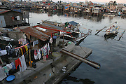 Manila Environs, Bayside. Manila is one of the largest and most densely populated cities in the world. Residents build house on stilts out over the numerous riverbanks and tributaries leading into the bay.