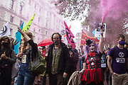 A clown holding a smoke grenade joins fellow climate activists from Extinction Rebellion at a 'Carnival of Corruption' protest against the government's facilitation and funding of the fossil fuel industry on 3 September 2020 in London, United Kingdom. Extinction Rebellion activists are attending a series of September Rebellion protests around the UK to call on politicians to back the Climate and Ecological Emergency Bill CEE Bill which requires, among other measures, a serious plan to deal with the UK's share of emissions and to halt critical rises in global temperatures and for ordinary people to be involved in future environmental planning by means of a Citizens' Assembly.