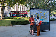With a London bus and the architecture of St Paul's Cathedral in the distance, visitors to London stop to view a detailed map of the City of London, the capital's historic financial district, on 8th September 2021, in London, England.