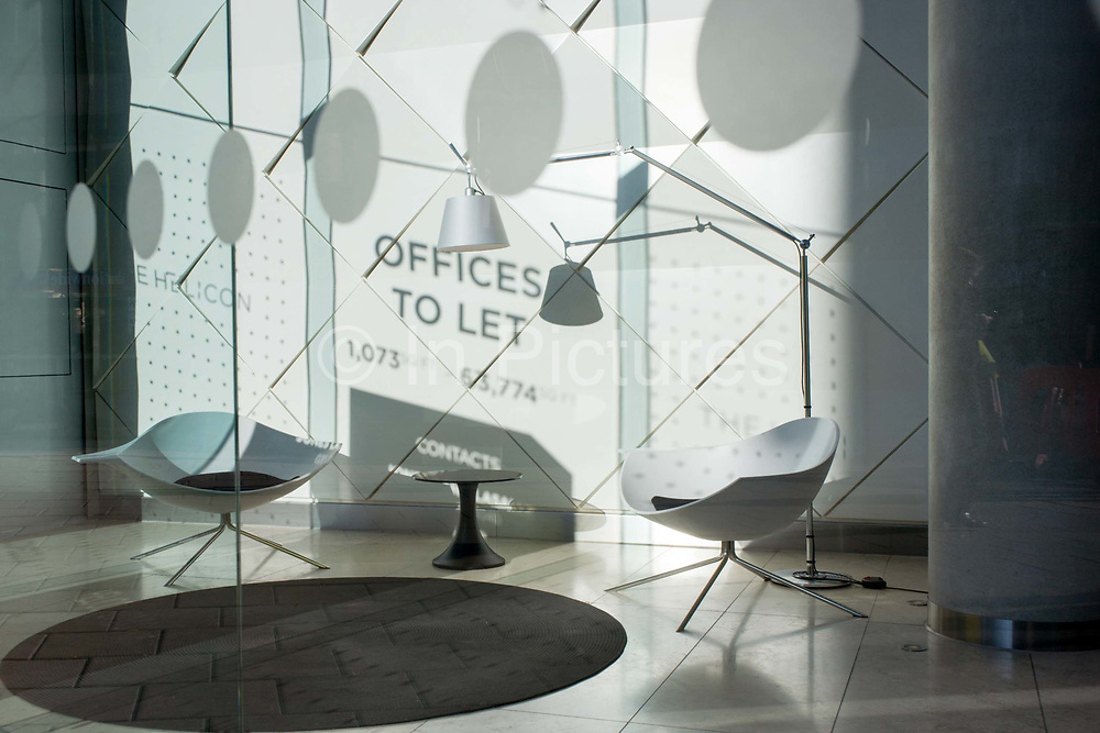 The shadows of a sign for Offices to Let is seen on a white wall in a corporate foyer in the City of London. Sunshine pours through the window of this generic company foyer window, allowing the shadow of lettering to be projected on to tht rear wall - advertising that this building has office space to let. Retro seats have been carefully postioned and there is a theme of spots and circles within the picture to emphasize design and coincidence. The amount of office space available to rent in central London has fallen by 14 per cent over the last 12 months and 48% since the peak (2009). Five million sq ft throughout 2014, but still remains at its lowest level for seven years. This is despite over 3 million sq ft completing construction during 2014.