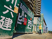 """15 FEBRUARY 2019 - SIHANOUKVILLE, CAMBODIA:  A Chinese worker goes into Blue Bay resort and casino, a Chinese construction project in Sihanoukville. There are about 80 Chinese casinos and resort hotels open in Sihanoukville and dozens more under construction. The casinos are changing the city, once a sleepy port on Southeast Asia's """"backpacker trail"""" into a booming city. The change is coming with a cost though. Many Cambodian residents of Sihanoukville  have lost their homes to make way for the casinos and the jobs are going to Chinese workers, brought in to build casinos and work in the casinos.      PHOTO BY JACK KURTZ"""