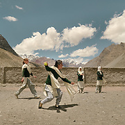 Girls play a game of cricket during school break. In the distance, a high-altitude trail leads into Afghanistan's Pamir Mountains.