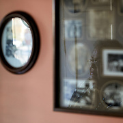 RALEIGH, NC - FEBRUARY 24: Lonnette Williams, a longtime resident of Raleigh, can be seen reflected in the glass of a collection of family pictures on the wall in the foyer of her home on February 24, 2019 in Raleigh, NC. (Logan Cyrus for The New York Times)