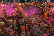 The gang of men from Barsana arrive to raid the Temple of Shriji, during Lathmar Holi. Men from Barsana raid the town whilst being assaulted with coloured water sprayed from rooftops, they are beaten by Nandgaon's women with large sticks and smeared with Holi coloured powders in a counterpart festival to the one held in Barsana on the previous day. The spectacle is a riot of colour amidst frenzied celebrations.
