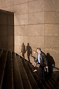 A couple climb steps next to the shadows of other anonymous people on a wall in Southwark, on the south side of London Bridge.