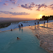 People swim in travertine pools in Pamukkale, Turkey