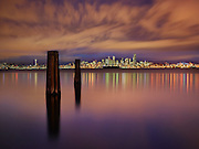 Light pollution, in all its glory here, lights the clouds over Seattle, which reflect back on the glassy waters of Elliott Bay. The still water serves as a mirror to add even more light to a cycle proving difficult to reverse. (Benjamin Benschneider / The Seattle Times)