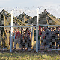 Illegal migrants stand next to the perimeter fence of a newly built migrant camp to replace the old one near Roszke (about 174 km South of capital city Budapest), Hungary on September 07, 2015. ATTILA VOLGYI