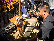 19 AUGUST 2015 - BANGKOK, THAILAND: People who lost family members in the Erawan Shrine bombing pray during a memorial service for members of a Malaysian family killed in the bombing of during the shrine's reopening. Erawan Shrine in Bangkok reopened Wednesday morning after more than 20 people were killed and more than 100 injured in a bombing at the shrine Monday, August 17, 2015. The shrine is a popular tourist attraction in the center of Bangkok's high end shopping district and is an important religious site for Thais. No one has claimed responsibility for the bombing.       PHOTO BY JACK KURTZ