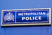 A metropolitan police station sign on the wall fo a police station, London. UK