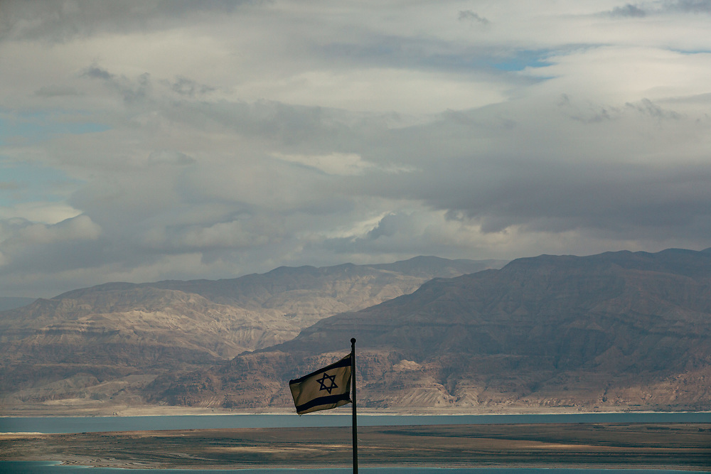 With a view of the Dead Sea in the background, an Israeli flag is seen from the ancient hilltop fortress of Masada in the Judean desert in Israel, on February 19, 2015. The ancient ruined desert fortress on a wind-swept plateau overlooking the Dead Sea is seen by many as an emblem of Israel's fighting spirit, it is believed to be the place where close to a thousand Jewish rebels killed themselves and each other about two millennia ago, rather than surrender and fall into slavery under the Romans.