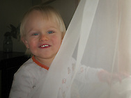 Ninteen month old toddler Talus Book teases his Grandpa with his clowning with a gauze curtain.