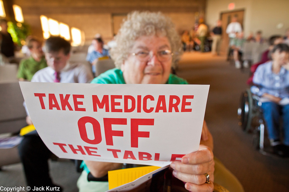 16 MAY 2011 - PHOENIX, AZ: TOBY STAHL, from Phoenix, AZ, holds up a sign supporting Medicare at a town hall meeting in Phoenix Monday. About 200 people attended Congressman Ben Quayle's (R-AZ) town hall meeting in the Anthem neighborhood of Phoenix, AZ, Monday. Quayle, son of former Vice President Dan Quayle, was elected in the Republican tide that captured the House of Representatives in Nov. 2010. Quayle tried to run under a Tea Party banner. Most of the people in the crowd were hostile to Quayle and the GOP budget proposal that would change medicare to a voucher system and Quayle was shouted down several times when he tried to support the budget.     Photo by Jack Kurtz