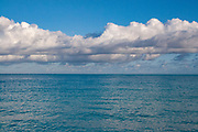 Clouds over an open sea with their reflections in the turquoise water