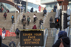 © Licensed to London News Pictures.19/03/2021. London,UK. Members of the public walk past the Covid-19 sign in Stratford, east London during the third national lockdown to prevent the spread of coronavirus. Lockdown restrictions are being relaxed over the coming weeks, following a significant drop in infections and deaths. Photo credit: Marcin Nowak/LNP