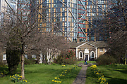 Hopton's Almshouses, Hopton Street, Southwark, London, UK. Tall glass buildings loom behind these historically important houses at Bankside and near to Tate Modern. Founded by Robert Hopton, fishmonger in 1730. Properties built around a garden in 1752 and are still in use. Before the days of state provision for the old, infirm or poor it was common for wealthy individuals to bequeath money or property to the local parish or to set up independent institutions to assist those in need locally.Many ancient parishes have such institutions and many almshouses still survive. However it is unusual to find one founded as early as 1752 still in its original form, carrying out its original function, so close to London.Hopton's Almshouses were founded from a trust set up by the will of Charles Hopton.