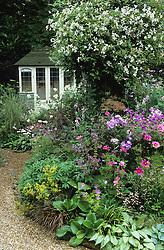 Summer border with summerhouse beyond. Clematis 'Alba Luxurians' growing through tree.
