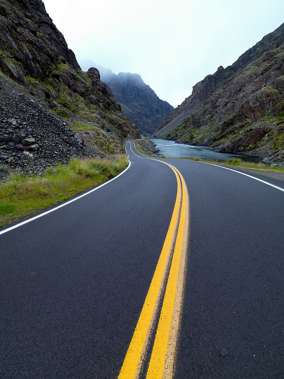 Newly painted double yellow lines on the Hells Canyon Dam Road along the Snake River with Idaho on the Left and Oregon on the Right.  Licensing and Open Edition Prints.