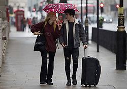 © Licensed to London News Pictures. 10/09/2021. Members of the public shelter form the rain underneath umbrellas in Westminster, central London.. Thunderstorms are expected across parts of the UK following a period of warm weather earlier this week. Photo credit: Ben Cawthra/LNP