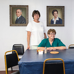 August 4, 2017 - Tangier Island, VA - Chesapeake House server and cook Fran Ellis and Barbara McReady (left to right) pose in front of portraits of previous proprietors of the Tangier Island restaurant.<br />  Photo by Susana Raab/Institute