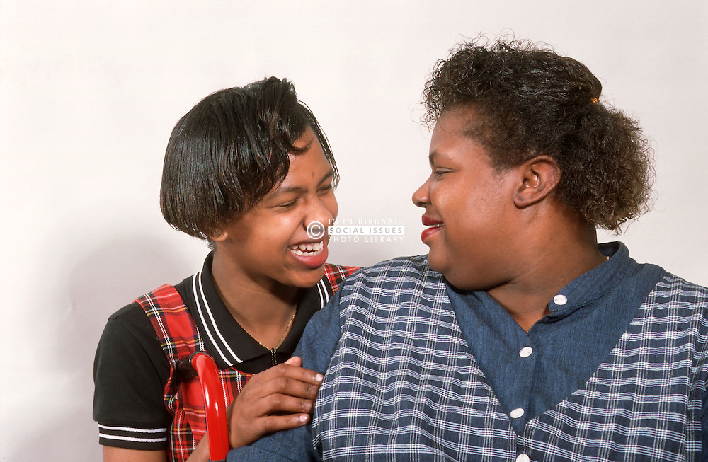 Woman with disability; who is wheelchair user; and teenage daughter smiling at each other,