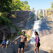 People climbing the rocks of Seven Wells waterfalls, Langkawi, Malaysia