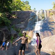 People climbing the rocks of Seven Wells waterfalls, Langkawi, Malaysia