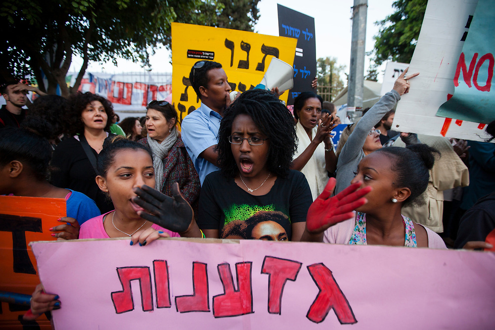 Israelis of Ethiopian origin and social rights activists hold banners and chant slogans during a demonstration against racism and discrimination in Jerusalem, Israel, on May 23, 2012. Ethiopian immigrants and other supporters gathered in front of Prime Minister Netanyahu's residence in Jerusalem, to protest what they say is racism directed towards the Ethiopian community in Israel.