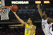 Trey Burke (3) of the University of Michigan Wolverines drives to the basket against the University of Kansas Jayhawks during the NCAA South Regionals at Cowboys Stadium in Arlington on Friday, March 29, 2013. (Cooper Neill/The Dallas Morning News)