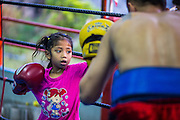 """18 DECEMBER 2104 - BANGKOK, THAILAND: A girl who wants to box works out with a boxer at the Kanisorn gym. The Kanisorn boxing gym is a small gym along the Wong Wian Yai - Samut Sakhon train tracks. Young people from the nearby communities come to the gym to learn Thai boxing. Muay Thai (Muai Thai) is a Thai fighting sport that uses stand-up striking along with various clinching techniques. It is sometimes known as """"the art of eight limbs"""" because it is characterized by the combined use of fists, elbows, knees, shins, being associated with a good physical preparation that makes a full-contact fighter very efficient. Muay Thai became widespread internationally in the twentieth century, when practitioners defeated notable practitioners of other martial arts. A professional league is governed by the World Muay Thai Council. Muay Thai is frequently seen as a way out of poverty for young Thais and Muay Thai camps and schools are frequently crowded. Muay Thai professionals and champions are often celebrities in Thailand.     PHOTO BY JACK KURTZ"""