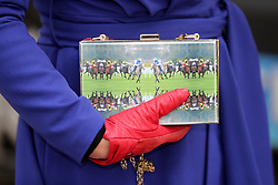 A racegoer holds a horse racing themed handbag during day two of the Punchestown Festival in Naas, Co. Kildare.