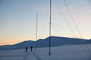 Mylène Jacquemart (left) and Michelle Blade pass radar antennas at the European Incoherent Scatter Scientific Association (EISCAT) facility on Breinosa, Spitsbergen, Svalbard.