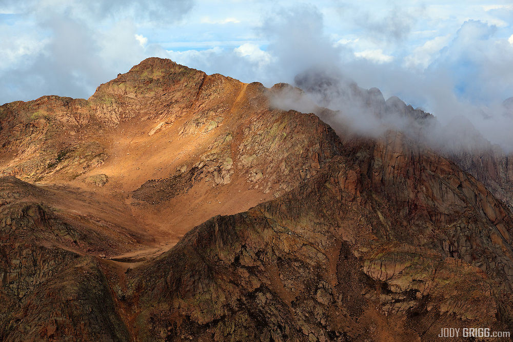 A break in the clouds supplies dappled light upon North Eolus 14,039ft.