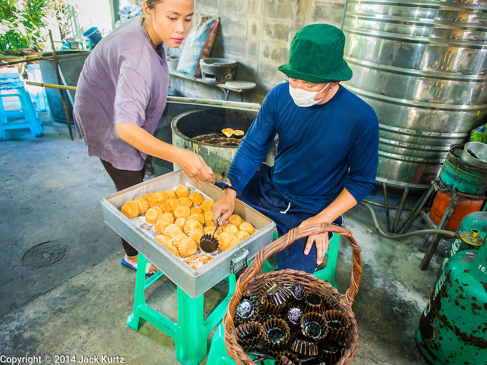 """28 OCTOBER 2014 - BANGKOK, THAILAND: Workers pull cakes out of the oven at the Pajonglak Maneeprasit Bakery in Bangkok. The cakes are called """"Kanom Farang Kudeejeen"""" or """"Chinese Monk Candy."""" The tradition of baking the cakes, about the size of a cupcake or muffin, started in Siam (now Thailand) in the 17th century AD when Portuguese Catholic priests accompanied Portuguese soldiers who assisted the Siamese in their wars with Burma. Several hundred Siamese (Thai) Buddhists converted to Catholicism and started baking the cakes. When the Siamese Empire in Ayutthaya was sacked by the Burmese the Portuguese and Thai Catholics fled to Thonburi, in what is now Bangkok. The Portuguese established a Catholic church near the new Siamese capital. Now just three families bake the cakes, using a recipe that is 400 years old and contains eggs, wheat flour, sugar, water and raisins. The same family has been baking the cakes at the Pajonglak Maneeprasit Bakery, near Santa Cruz Church, for more than 245 years. There are still a large number of Thai Catholics living in the neighborhood around the church.   PHOTO BY JACK KURTZ"""