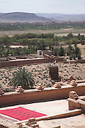 Red rug drying on roof terrace The kasbah of Taourirt, Ouarzazate, Morocco, north Africa with view over Draa river valley